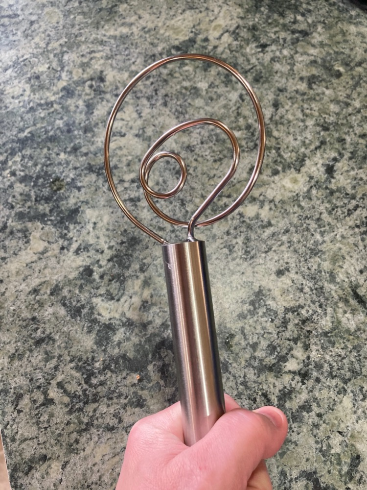post author's hand holding up a bread whisk